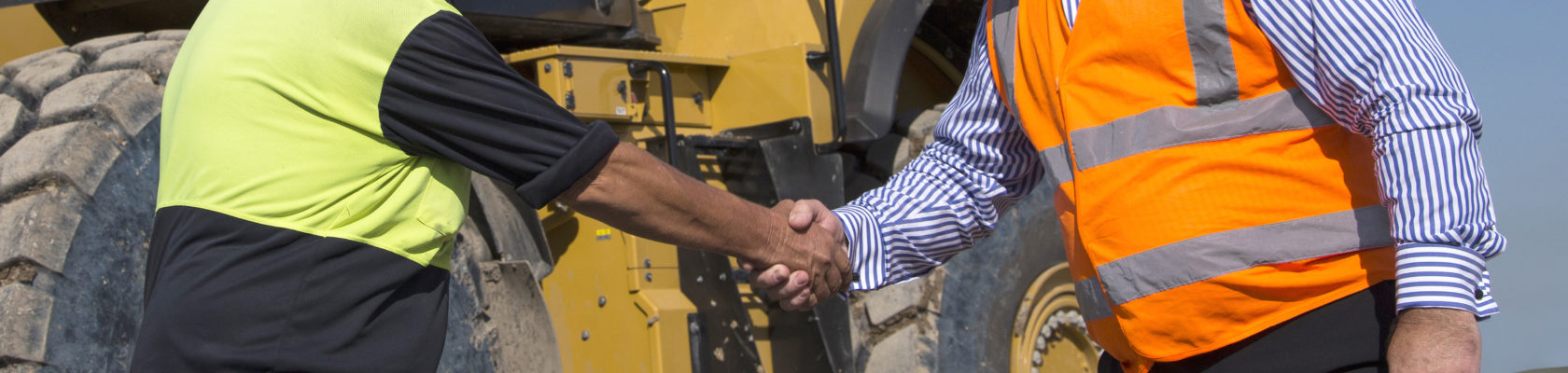 Two men shaking hands in front of Cat machine